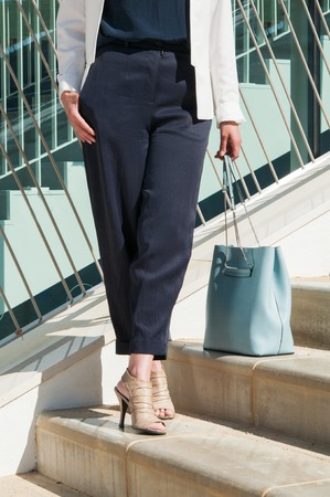 Medium shot of female crisscrossed legs in black trousers with blue bag standing at stairs. Front view. Lifestyle concept