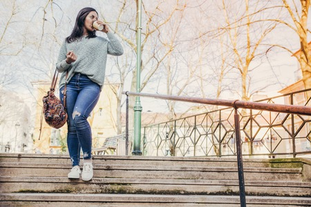 Young woman walking down city stairs and drinking coffee. Pretty lady wearing casual clothes, holding drink in disposable cup and backpack. Urban lifestyle concept. Front view.
