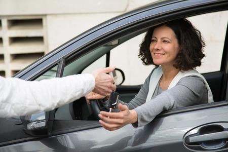 Coche de compra de empresaria positiva. Mujer joven sonriente que cuelga de la ventana lateral del coche y que recibe la llave del vendedor anónimo. Concepto de compra de vehículos