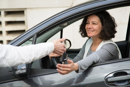 Positive businesswoman purchasing car. Smiling young woman hanging out of car side window and receiving key from anonymous seller. Vehicle purchase concept