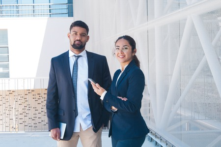 Colleagues posing, holding tablet and smartphone outdoors. Business man and woman looking at camera with building wall and railing in background. Business people and break concept. Front view.