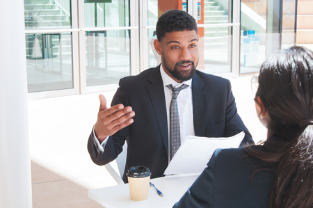 Businessman gesturing and talking with partner in outdoor cafe. Business man sitting and talking with woman who is sitting back to camera with building glass wall in background. Negotiations concept.