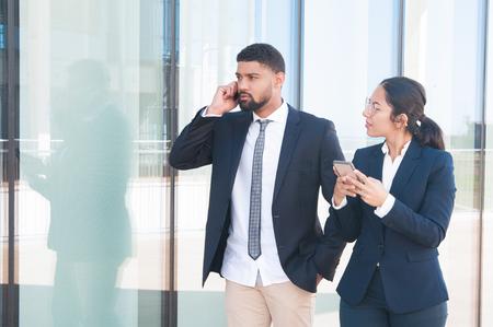 Jonge succesvolle zakenmensen die smartphones buitenshuis gebruiken. Jonge vrouw in formeel pak die haar gadget vasthoudt en naar collega kijkt, die op de cel spreekt. Telefoon gebruikers concept