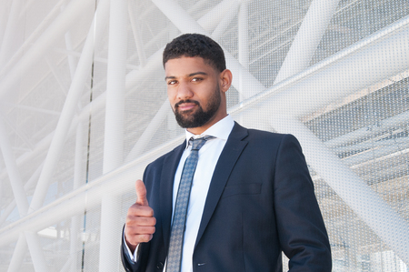 Serious black business man showing thumb up. Guy standing with building constructions in background. Promotion concept. Front view.