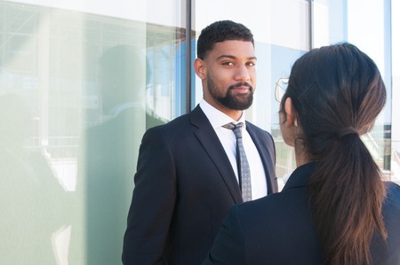 Positive business leader discussing project with coworker outdoors. Young man in office suit smiling at camera while talking to female colleague. Coworkers outside concept