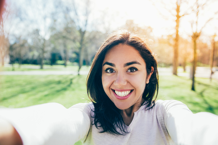 Selfie of smiling excited girl walking outdoors. Happy joyful young woman taking picture of herself in city park. Euphoria concept