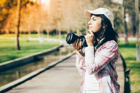 Pensive inspired photographer waiting moment for picture. Young woman wearing casual shirt and cap holding photo camera at face and looking away. Occupation concept
