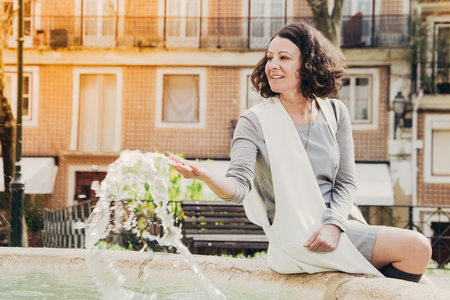 Smiling inspired lady in casual enjoying leisure time and having fun outdoors. Young woman resting at fountain and splashing water. Urban environment concept 免版税图像