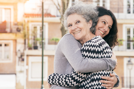 Joyful mother and daughter saying goodbye to each other. Young and senior woman smiling and hugging. Hug concept Banque d'images