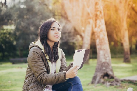 Inspired Asian girl writing down thoughts while working in park. Pensive young woman in jacket sitting in park and looking away. Planning concept 免版税图像