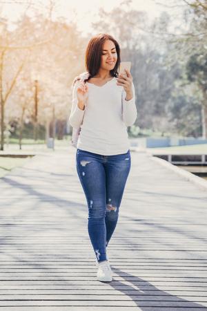 Konzentriertes positives Mädchen, das am Telefon plaudert. Schöne junge Frau in lässigem Lächeln auf dem Smartphone-Bildschirm, während sie den Fußweg im Park entlang geht. Kommunikationskonzept Standard-Bild