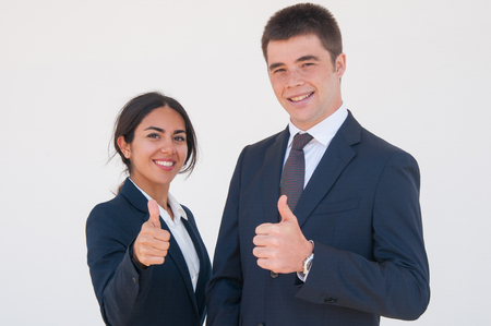Positive confident business colleagues showing thumbs up. Young man and woman in formal jackets smiling at camera and expressing approval. Successful career concept