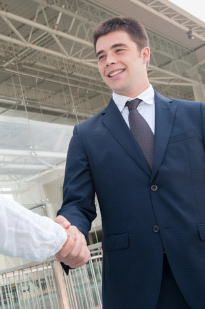 Happy successful professional meeting colleague in office corridor. Young man in formal jacket and tie shaking hands with coworker. Handshake concept