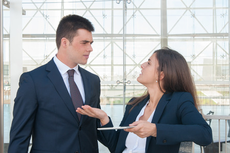 Pretty serious woman in white blouse and concentrated young man in dark suite standing in office corridor, woman showing data on tablet, they arguing. Work, communication concept