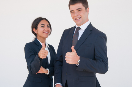Happy confident professionals expressing approval. Young man and woman in formal suits smiling at camera and showing thumbs up. Positive feedback concept