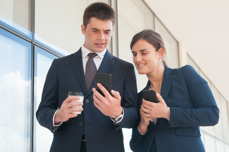Verbaasde manager met afhaalbeker die smartphonescherm toont aan vrouwelijke collega. Twee collega's met telefoons die nieuws delen tijdens de koffiepauze. Nieuwsconcept delen Stockfoto