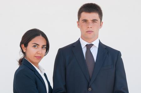 Poważni koledzy z pracy udanej pozowanie na białym tle. Portret młodego mężczyzny i kobiety w formalnych garniturach. Koncepcja zespołu biznesowego