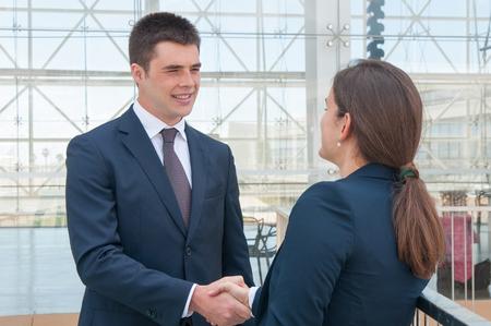 Due colleghi che si salutano sulla terrazza dell'ufficio. Giovane uomo e donna in abiti formali handshake. Concetto di comunicazione aziendale Archivio Fotografico