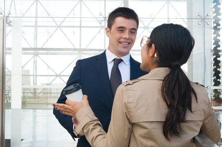 Happy business people gesturing and discussing ideas outdoors. Business man talking with woman who is standing back to camera with building glass wall in background. Colleagues or partners concept. Banque d'images
