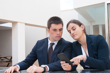 Business woman showing information on phone screen to coworker. Business man and woman wearing formal clothes and sitting at cafe table. Business news concept.