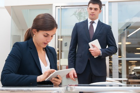 Business woman using tablet and her colleague standing near. Business woman sitting at desk and man standing and holding tablet computer. Business people and technology concept.