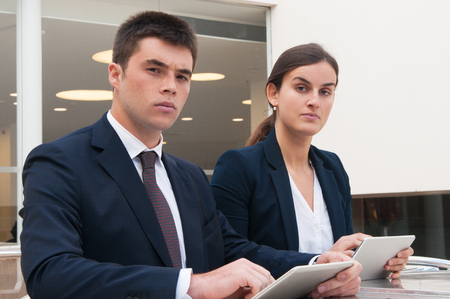 Colleagues looking at camera and holding tablets at desk. Business man and woman wearing formal clothes and sitting at cafe table. Technology in business concept.