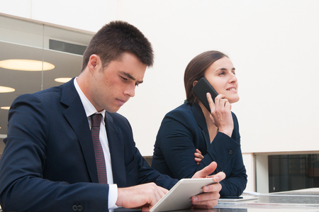 Colleagues using tablet and calling on phone at desk outdoors. Business man and woman wearing formal clothes and sitting at cafe table. Business and communication concept. Stockfoto