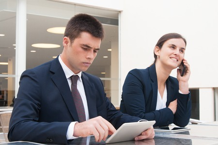 Colleagues using tablet and talking on phone at desk outdoors. Business man and woman wearing formal clothes and sitting at cafe table. Business and communication concept.