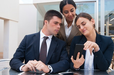 Smiling business woman showing smartphone screen to colleagues. Business man and women reading news, standing and sitting at cafe table. Business news concept. Front view.