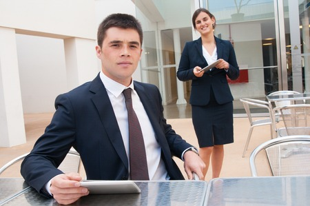 Smiling colleagues holding tablets and posing at camera in outdoor cafe. Business man sitting at desk and woman standing near him. Colleagues concept. Front view.