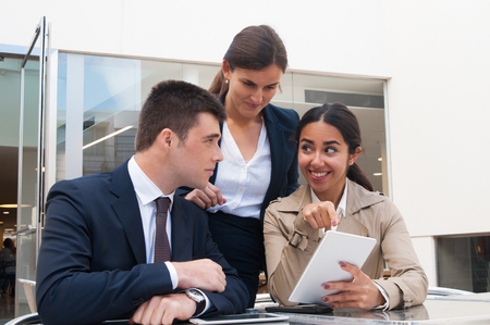 Smiling young woman showing tablet screen to business people. Business man and women discussing issues, standing and sitting at cafe table. Partnership concept. Front view.