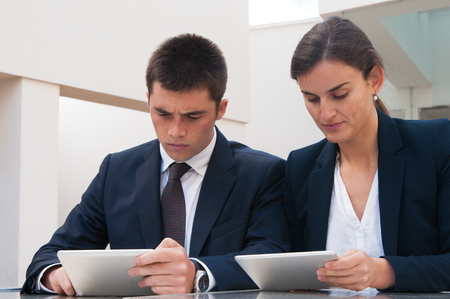 Serious business people working on tablet computers at desk. Business man and woman wearing formal clothes and sitting at cafe table. Technology in business concept. Front view. Stockfoto