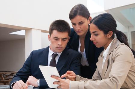 Ernste Frau, die Geschäftsleuten Tablet-Bildschirm zeigt. Geschäftsmann und Frauen diskutieren über Probleme, stehen und sitzen am Café-Tisch. Bestellkonzept. Vorderansicht. Standard-Bild