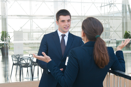 Smiling business man talking with female colleague outdoors. Business man and woman who is standing back to camera with glass wall in background. Break and communication concept. Stockfoto