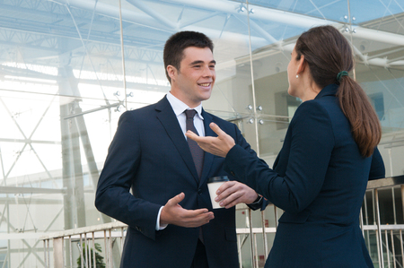 Smiling business people gesturing and chatting outdoors. Business man and woman talking with railing and building glass wall in background. Break and communication concept. Side view.