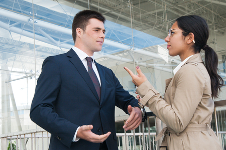Serious business people gesturing and discussing issues outdoors. Business man and woman talking with railing and building glass wall in background. Colleagues or partners concept. Side view. Stockfoto