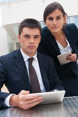 Serious business people posing at camera and holding tablets at desk. Business man and woman wearing formal clothes, standing and sitting at cafe table. Technology in business concept. Front view. Stockfoto
