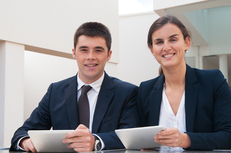 Smiling business people looking at camera and holding tablets at desk. Business man and woman wearing formal clothes and sitting at cafe table. Technology in business concept. Front view.
