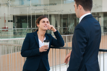 Relaxed business man and woman chatting outdoors. Colleagues talking with railing and building glass wall in background. Break and communication concept. Side view.