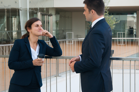 Relaxed business woman and man chatting outdoors. Colleagues talking with railing and building glass wall in background. Break and communication concept. Side view. Stockfoto