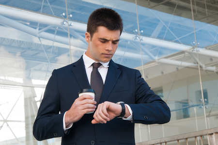 Serious business man checking time on watch outdoors. Handsome guy holding plastic coffee cup and standing with building glass wall in background. Business appointment concept. Front view. Stockfoto