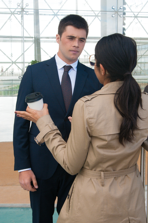 Serious business people gesturing and discussing ideas outdoors. Business man talking with woman who is standing back to camera with building glass wall in background. Colleagues or partners concept. Stockfoto