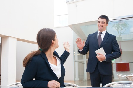Happy business people meeting and greeting each other outdoors. Business woman sitting and man standing and waving his hand. Business people meeting concept.