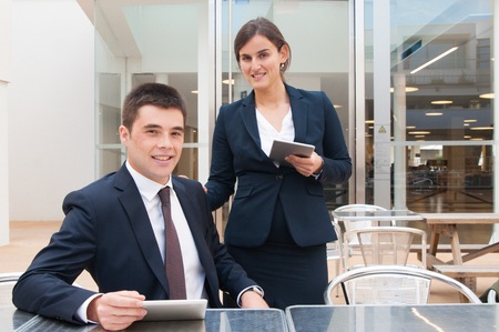Happy colleagues holding tablets and posing at camera outdoors. Business man sitting at desk and woman standing and holding hand on his shoulder. Business team or colleagues concept. Front view.