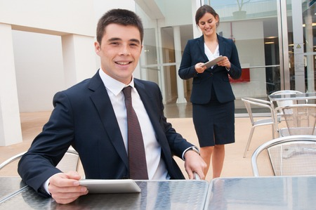 Happy colleagues holding tablets in outdoor cafe. Business man sitting at desk and woman standing near him. Colleagues concept. Front view.