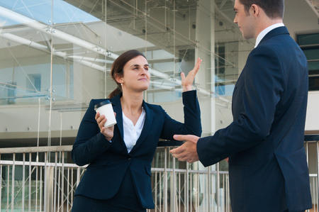 Relaxed business man and woman chatting and gesturing outdoors. Colleagues talking with railing and building glass wall in background. Break and communication concept. Side view.