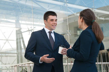 Positive business people gesturing and chatting outdoors. Business man and woman talking with railing and building glass wall in background. Break and communication concept. Side view.