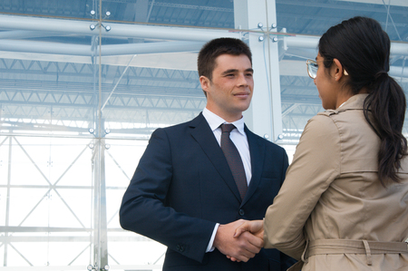 Positive business people meeting and shaking hands outdoors. Business man greeting woman who is standing back to camera with building glass wall in background. Colleagues or partners concept. Stockfoto
