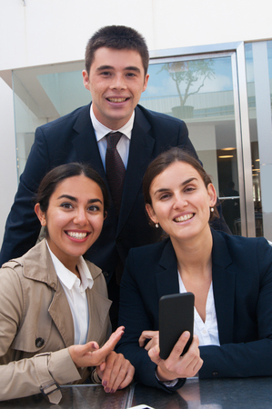 Positive business people posing at camera at desk outdoors. Business man and women using smartphone, standing and sitting at cafe table. Business people and news concept. Front view.