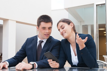 Positive business woman showing smartphone screen to colleague. Business man and woman wearing formal clothes, discussing news and sitting at cafe table. Business news concept. Stockfoto
